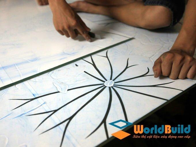 Người thợ dùng dao tách đường nét và phân mảng khối để chuyển thể tranh ảnh sang tranh kính.